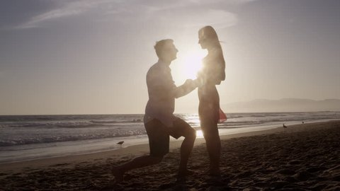 Romantic Silhouette of Man Getting Down on his Knee and Proposing to Woman on Beach - Couple Gets Engaged at Sunset - Man Putting Ring on Girl's Finger