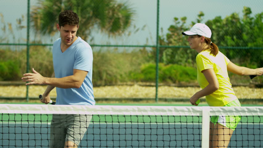 Caucasian couple enjoying healthy outdoors lifestyle holding racquets warming up for tennis game shot on RED EPIC | Shutterstock HD Video #6757855