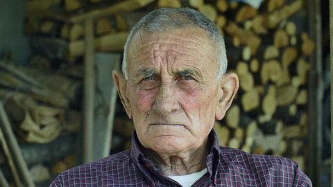 serious wrinkled old man with firewood in background: 4k portrait