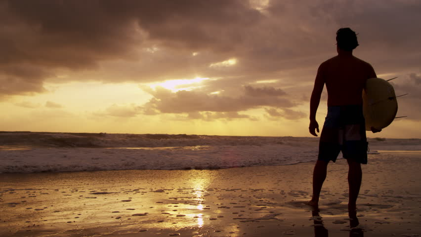 Silhouette solitary young male surfer standing sand beach sunset holding surfboard watching ocean waves shot on RED EPIC