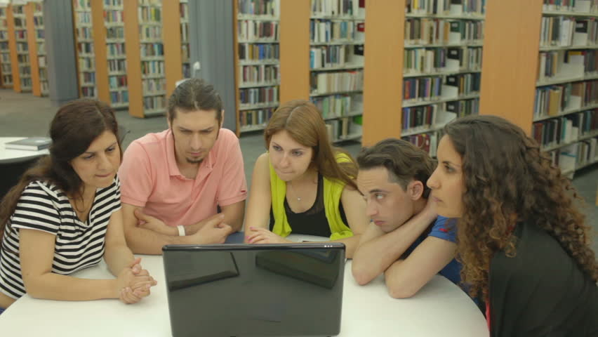 Five group mates watching training video in the library