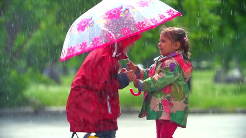 Girl letting boy under her umbrella