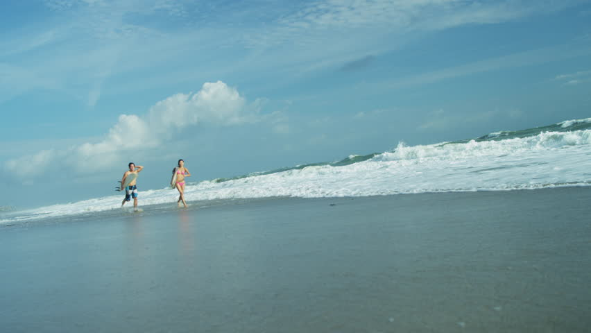 Healthy young Asian Chinese couple swimwear laughing together holding surfboards running into waves shot on RED EPIC | Shutterstock HD Video #6810985