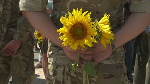 Flower in the hands of a soldier.