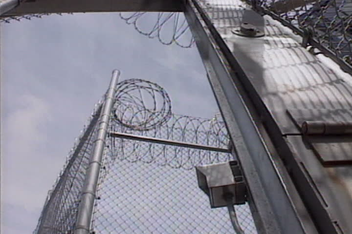 Gates at a prison yard slam shut.