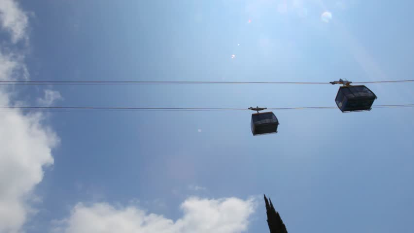 Two Cabins Moving On Funicular Against Sky With Sun Above Trees Sochi Russia