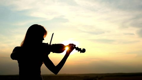 Silhouette girl violinist playing the violin at sunset sky background. Long shot. Color v.1