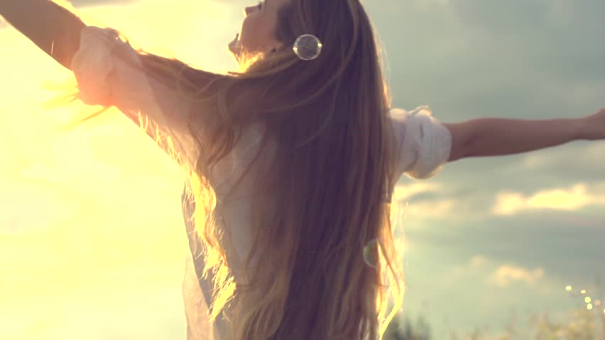 Happy girl with long hair having fun outdoor. Beauty girl spinning, laughing and catching soap bubbles. Countryside. Nature. Freedom. Slow motion video footage 1080p full HD. High speed camera shot