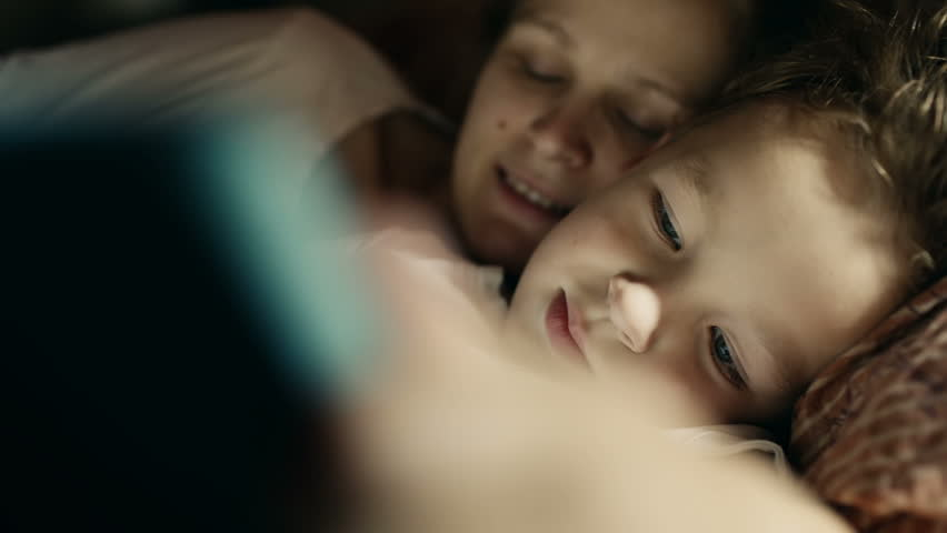 Close-up shot of son and mother in bed playing game on touch pad. Bedtime entertainment