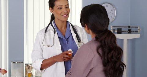 Black doctor explaining prescription medicine to female patient