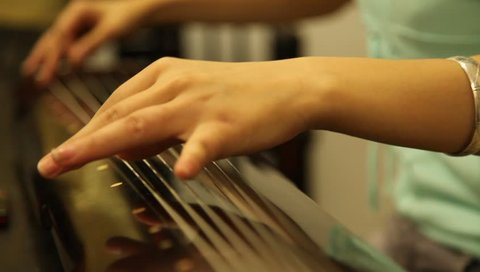 Chengdu, China - August 10: A woman plays traditional Chinese musical instrument during music lesson, August 10, 2009