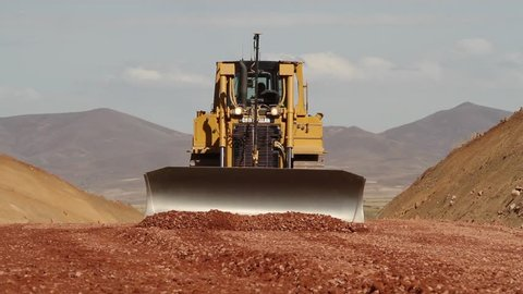 ANTOFAGASTA, CHILE - OPEN PIT MINE - A Caterpillar Retro-excavator drives towards the camera while shoveling sand in front of it.