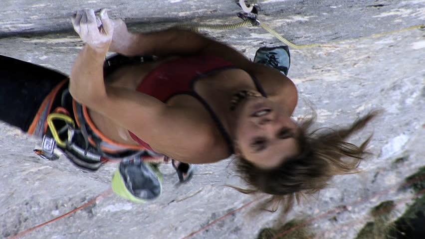 A female climber climbs up a steep rock