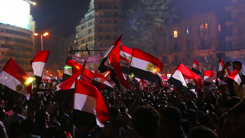 Protestors wave the Egyptian flag in Cairo, Egypt at a large nighttime rally.