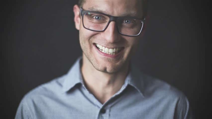77d29082ebc Portrait of young casual man with glasses smiling in front of camera. Young  handsome man in navy shirt and glasses laughing against dark background