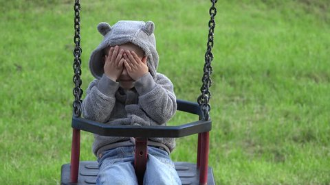 Funny child playing hide and seek, smiling boy swinging in a rocking chair