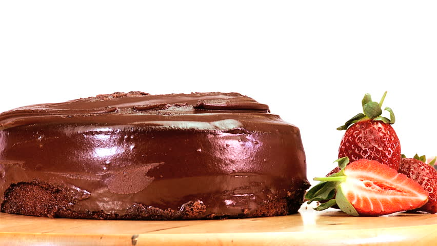 A serving of indulgent sticky chocolate cake served with fresh strawberries