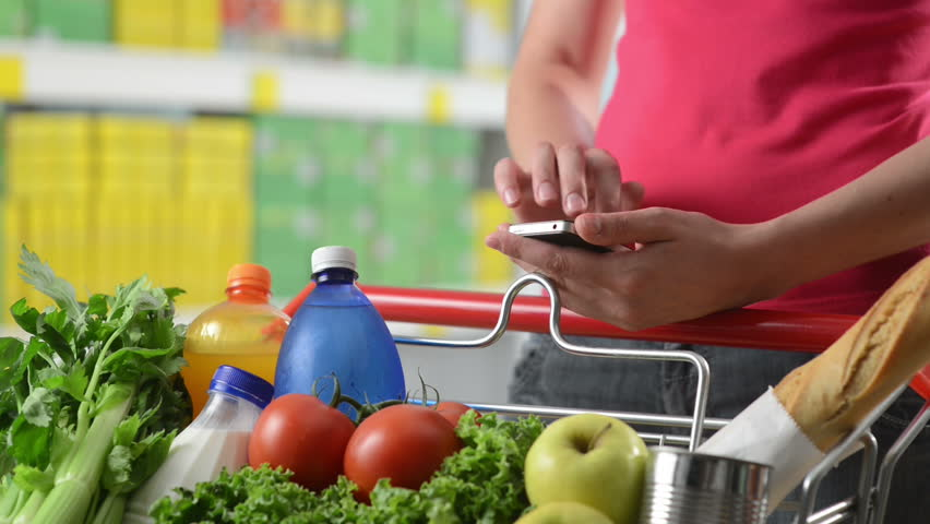 Woman using mobile phone at supermarket hands close-up. | Shutterstock HD Video #7135981