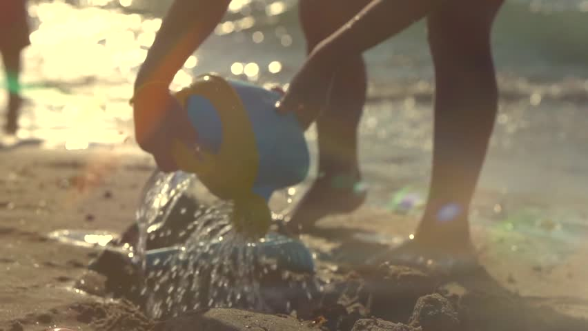 A Little Girl Having Fun with a Sand and Sear water. Silhouette of a Child Playing with Toys on the Seashore. Funny little girl Making a Sand Castle on a Sandy Beach. Slowmotion full HD 1080p 240 fps | Shutterstock HD Video #7139005