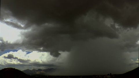 Time Lapse, Rain shafts, dark clouds, drop rain over foggy mountains when burst of sunlight highlights city of Tucson skyline during summer monsoon storm. 1080p