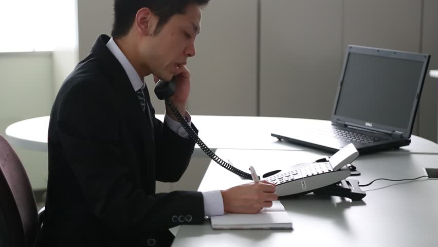 Japanese businessman apologizing on the phone in the office
