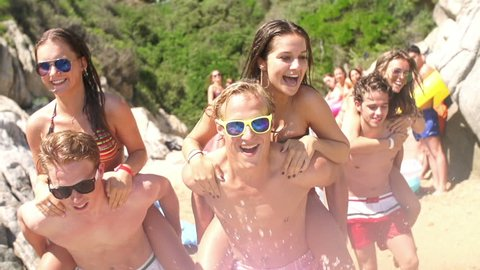 Friends giving piggyback rides to girls at the beach in slow motion
