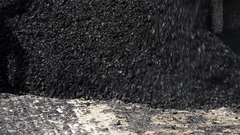 Close up asphalt. Asphalt paver machine during road construction. Tracked machines for paving apply asphalt to road. Spillage of asphalt on the street. Pouring blacktopping. Road work, street repair.