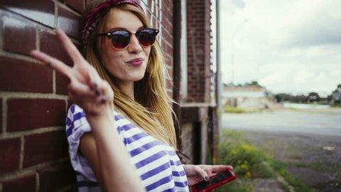 teenage girl texting at grungy wall showing peace sign