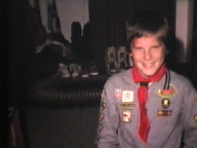 A proud young boy scout shows off his awards after attending a special Cub Scout camp.