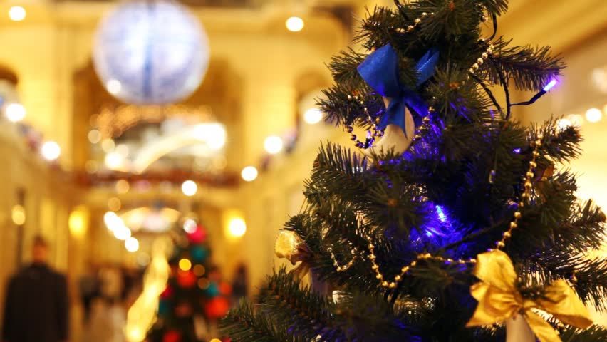 close up New Year's tree with blinking dark blue garlands in shopping centre