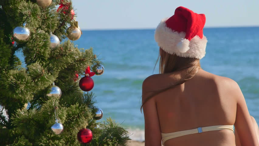 79b2a1cfef7 Girl in red Santa hat near Christmas tree on the tropical beach rear view
