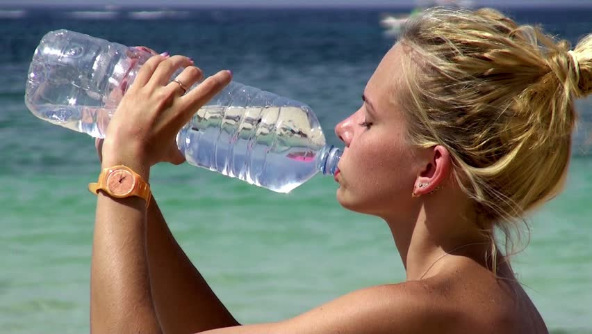 Pretty girl on the beach by the sea drinks water.