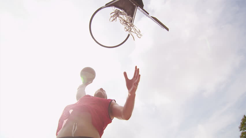 Male basketball player slam dunking on an outdoor basketball court on a sunny day, shot on RED EPIC