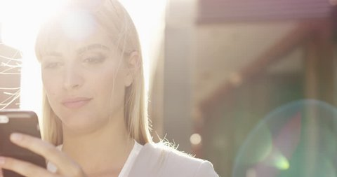 Beautiful blonde woman using smartphone solar flare sunlight energy concept - RED EPIC DRAGON 6K