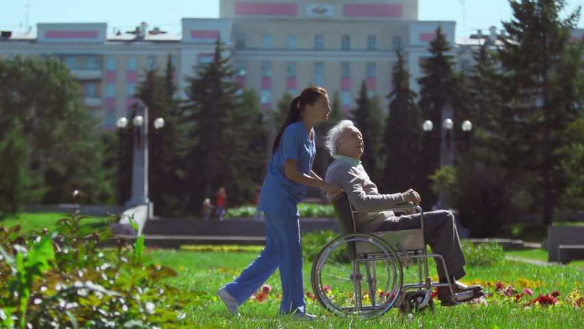 Nurse with patient in wheelchair passing by camera in slow motion