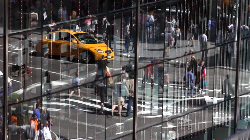 Unique view of a city intersection, through a reflection on a city skyscraper.