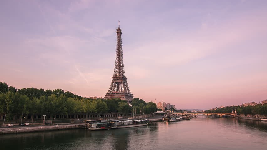 Eiffel tower seen from a bridge on the seine river,timelapse from night to day,paris wakes up as the sun rise up 4k
