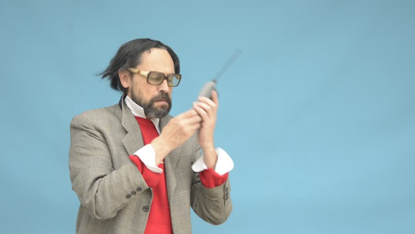An untidy bizarre man, wearing big patched glasses and a toupee, trying to answer an incoming phone call on an antique big cellphone, over light blue background