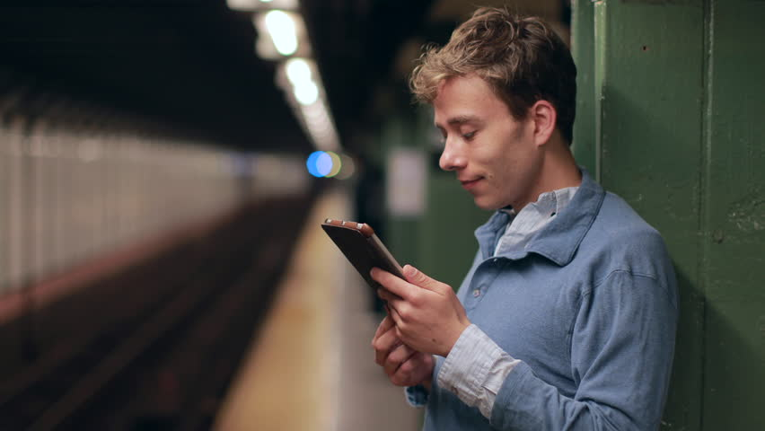 Young caucasian man using tablet pc on subway platform | Shutterstock HD Video #7451560