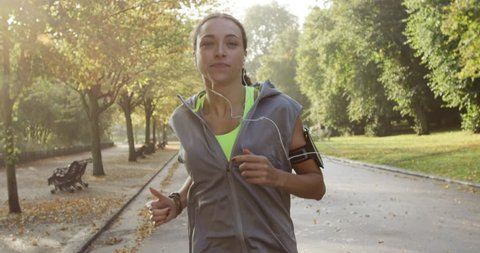 Runner woman running in park exercising outdoors fitness tracker wearable technology
