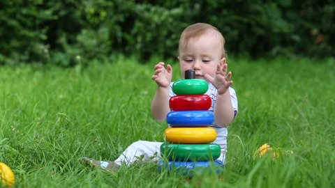 Happy baby plays with toys on fresh green grass of meadow