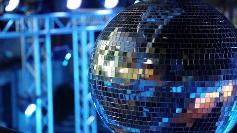 Blue spinning glitterball on dancefloor