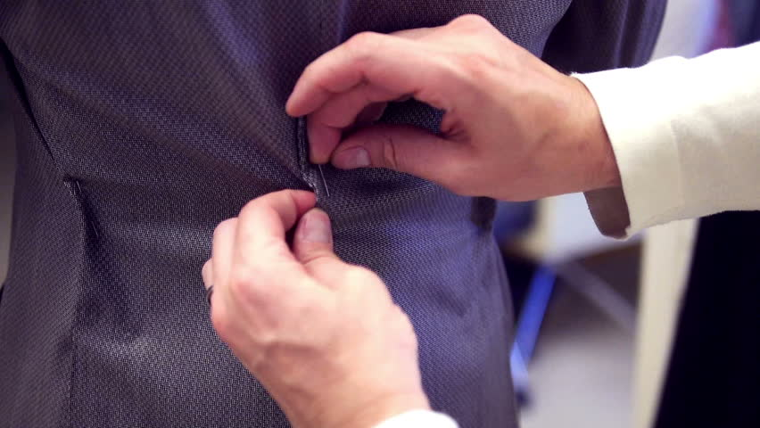Tailor's nimble hands carefully working on a suit at a fashion boutique. Close up. Hands only.