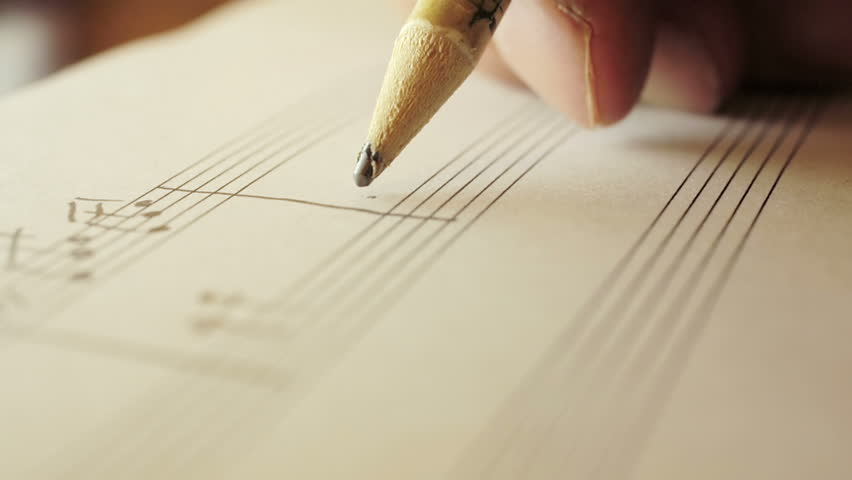 writing notes on staff: musician is composing with pencil