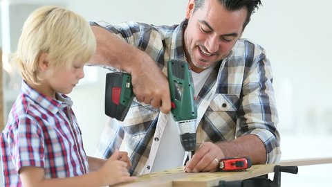 Man with little boy using electric drill