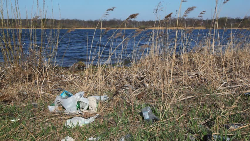 household rubbish on spring polluted bank of river