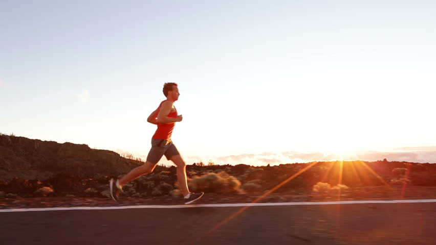 Runner - athlete man running training outdoors exercising on mountain road at sunset in amazing landscape nature. Fit handsome athletic male working out for marathon run outside in summer. | Shutterstock HD Video #7587916