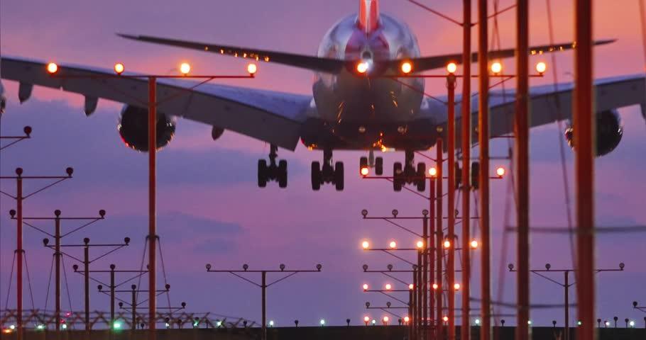 Jumbo jet airplane plane landing in airport in Los Angeles at sunset. 4K.