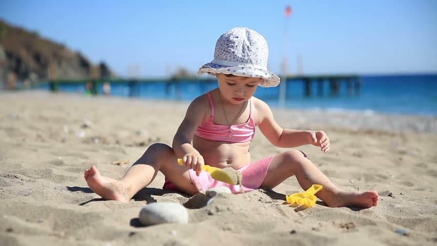 Little girl in pink swimsuit playing with sand on the beach. | Shutterstock HD Video #7633075