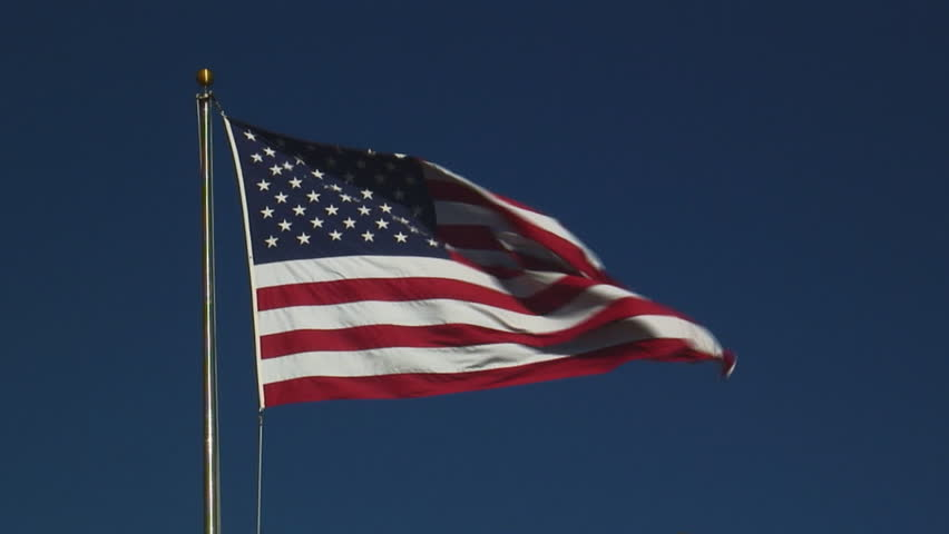 real United States of America flag flying on flagpole against clear blue sky - HD, no audio, medium shot